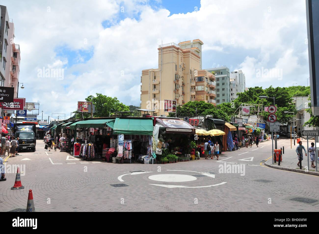 Boutiques en plein air, les panneaux publicitaires, les consommateurs et camion de livraison à un carrefour Photo Stock