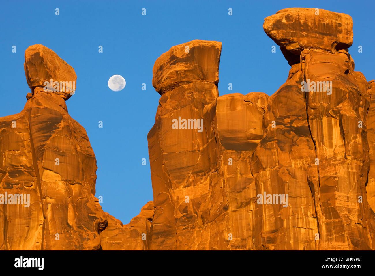 Près de la pleine lune avec les trois commères, Arches National Park, près de Moab, Utah. Photo Stock
