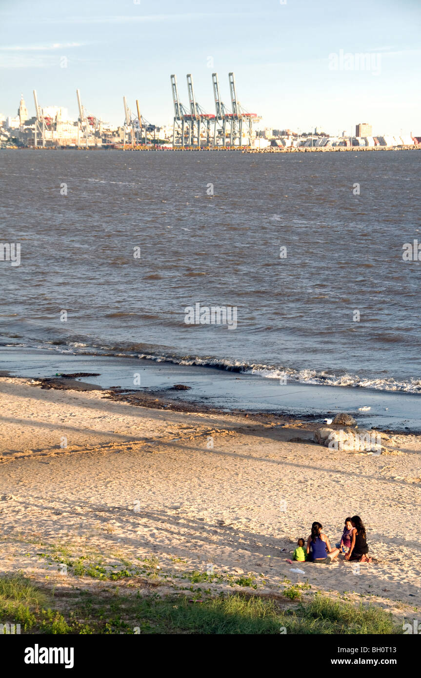 L'Uruguay. Les gens de soleil à Cerro beach, avec vue sur le port de Montevideo, Photo Stock