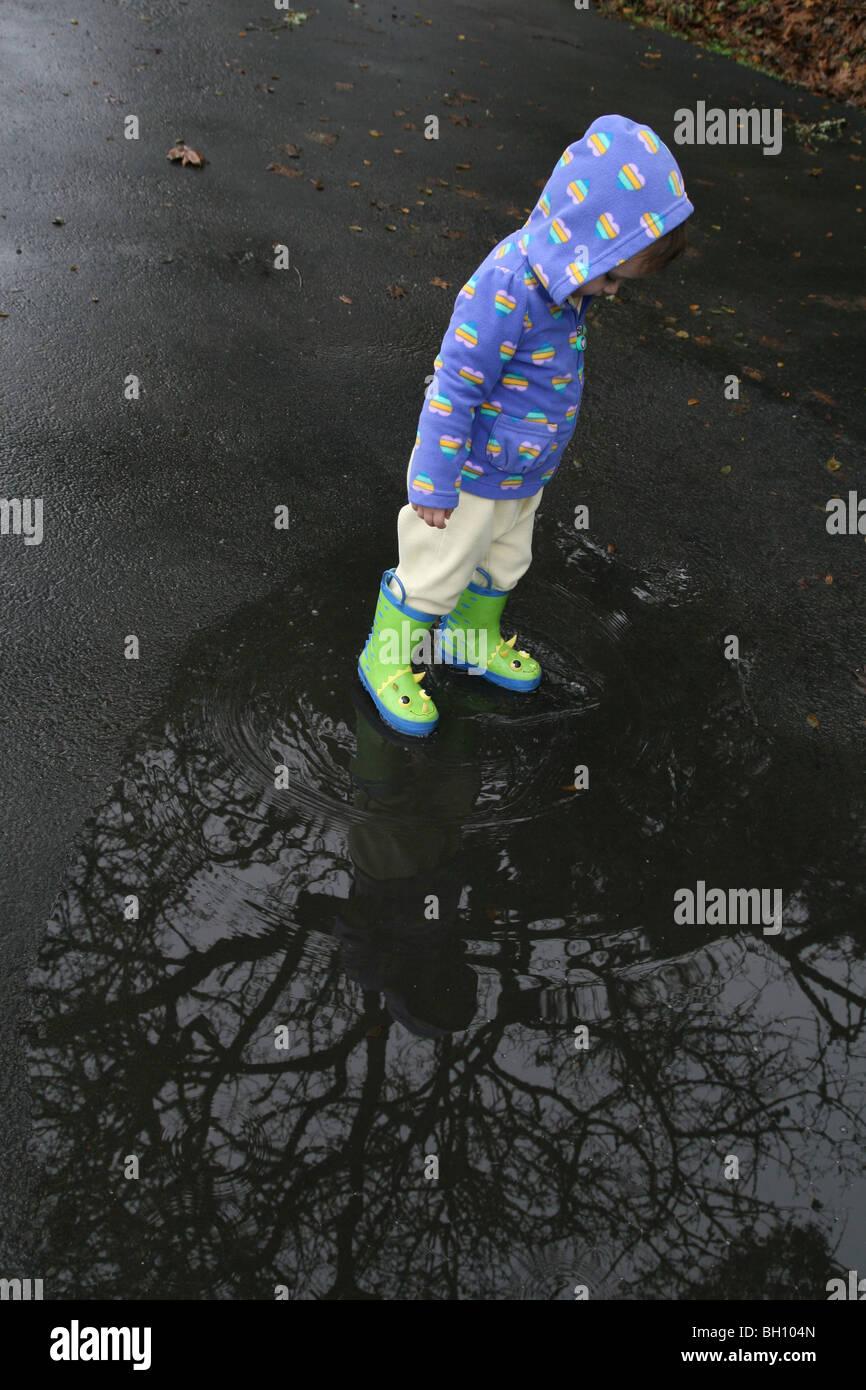 Un jeune enfant marche dans une flaque de pluie. Banque D'Images