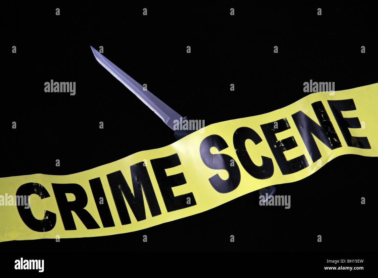 Scène de crime (ne pas traverser) ruban allongé sur un couteau de cuisine dentelé. Royaume-uni (UK). Photo Stock
