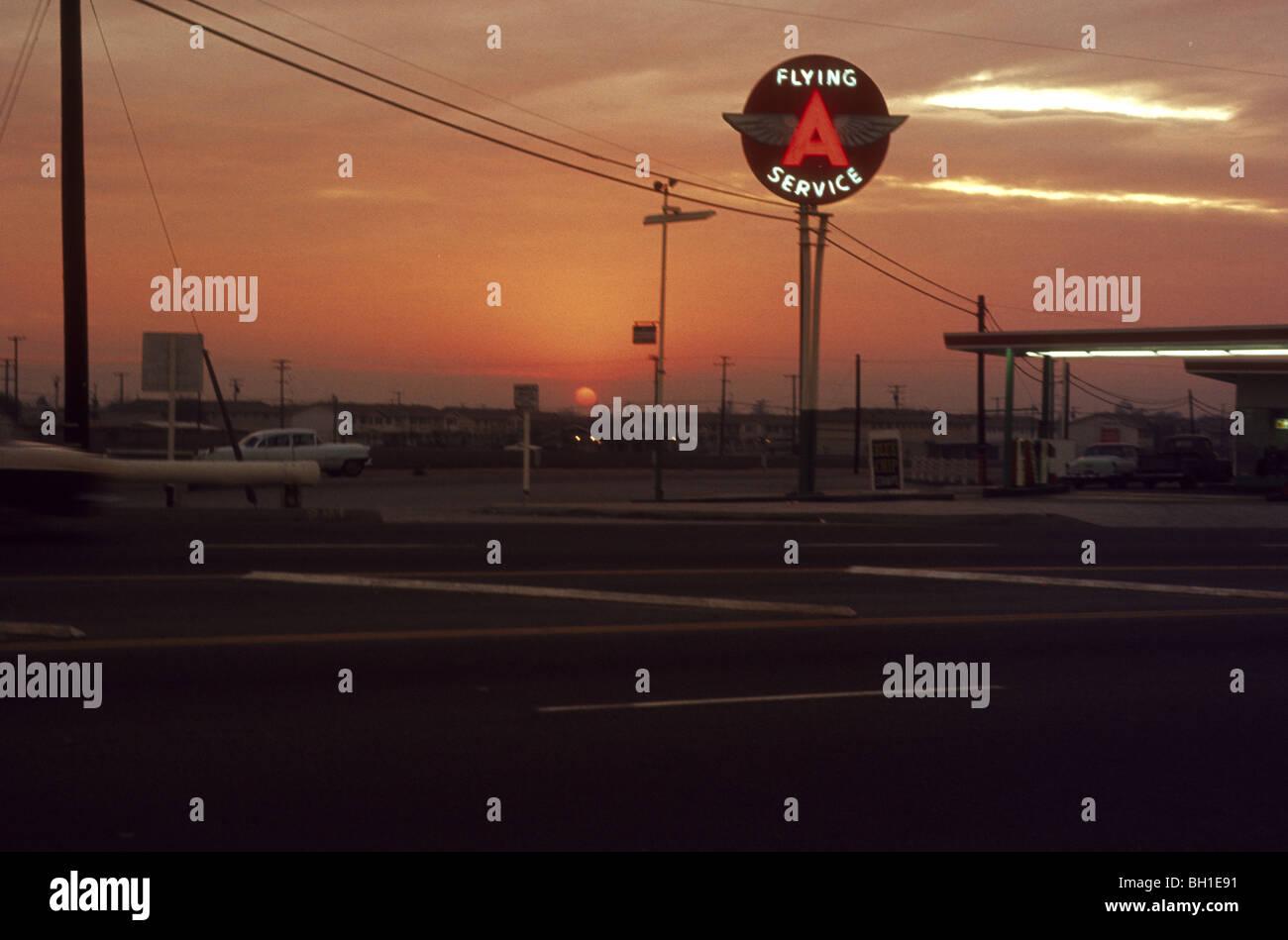 Essence d'une station-service de vol avec des ailes signe au lever du soleil coucher du soleil en 1964. Los Photo Stock