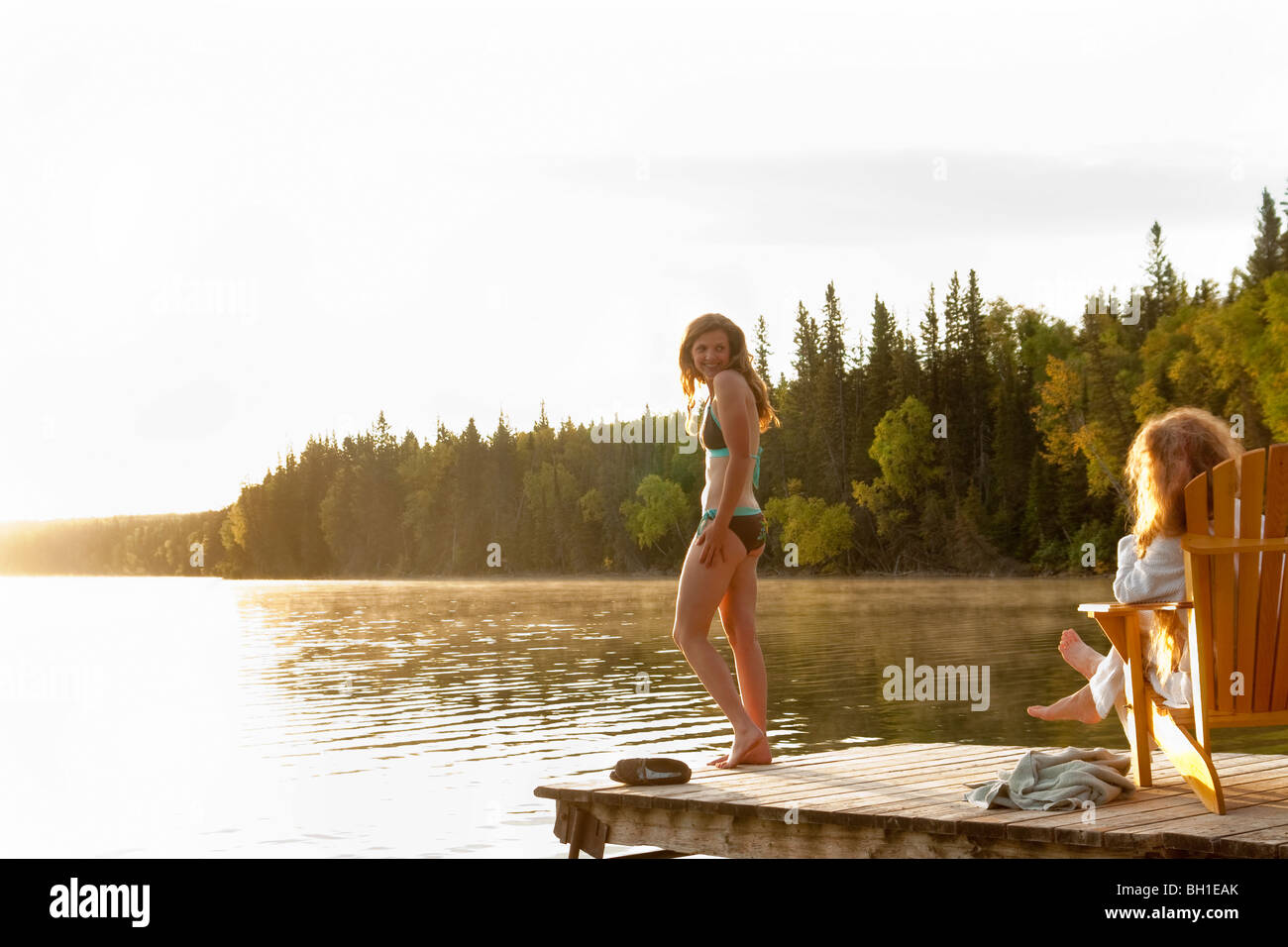 Femme debout en maillot, deuxième femme assise dans une chaise sur dock, Clear Lake, Manitoba, Canada Banque D'Images