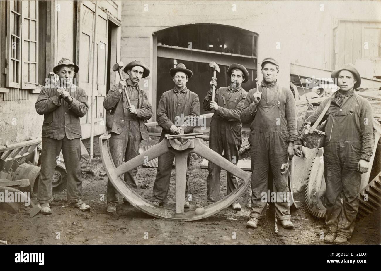 Six ouvriers agricoles et la moitié des roues industrielles géantes Photo Stock