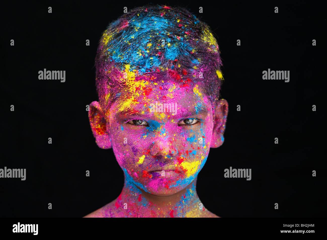 Jeune garçon indien graves couvertes en pigment poudre de couleur sur un fond noir. L'Inde Banque D'Images