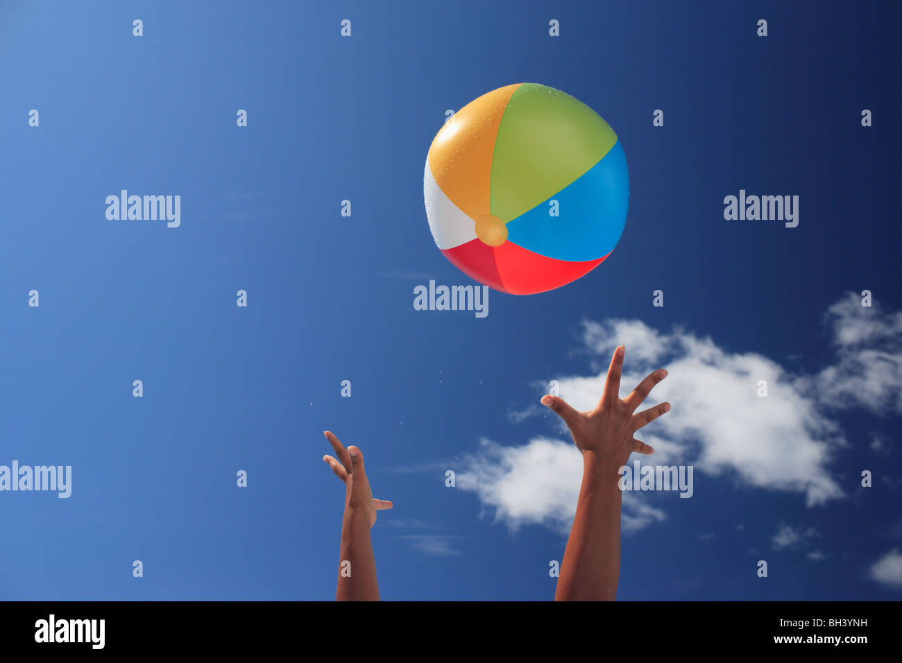 Les mains d'une femme jetant un ballon de plage gonflable dans l'air Photo Stock
