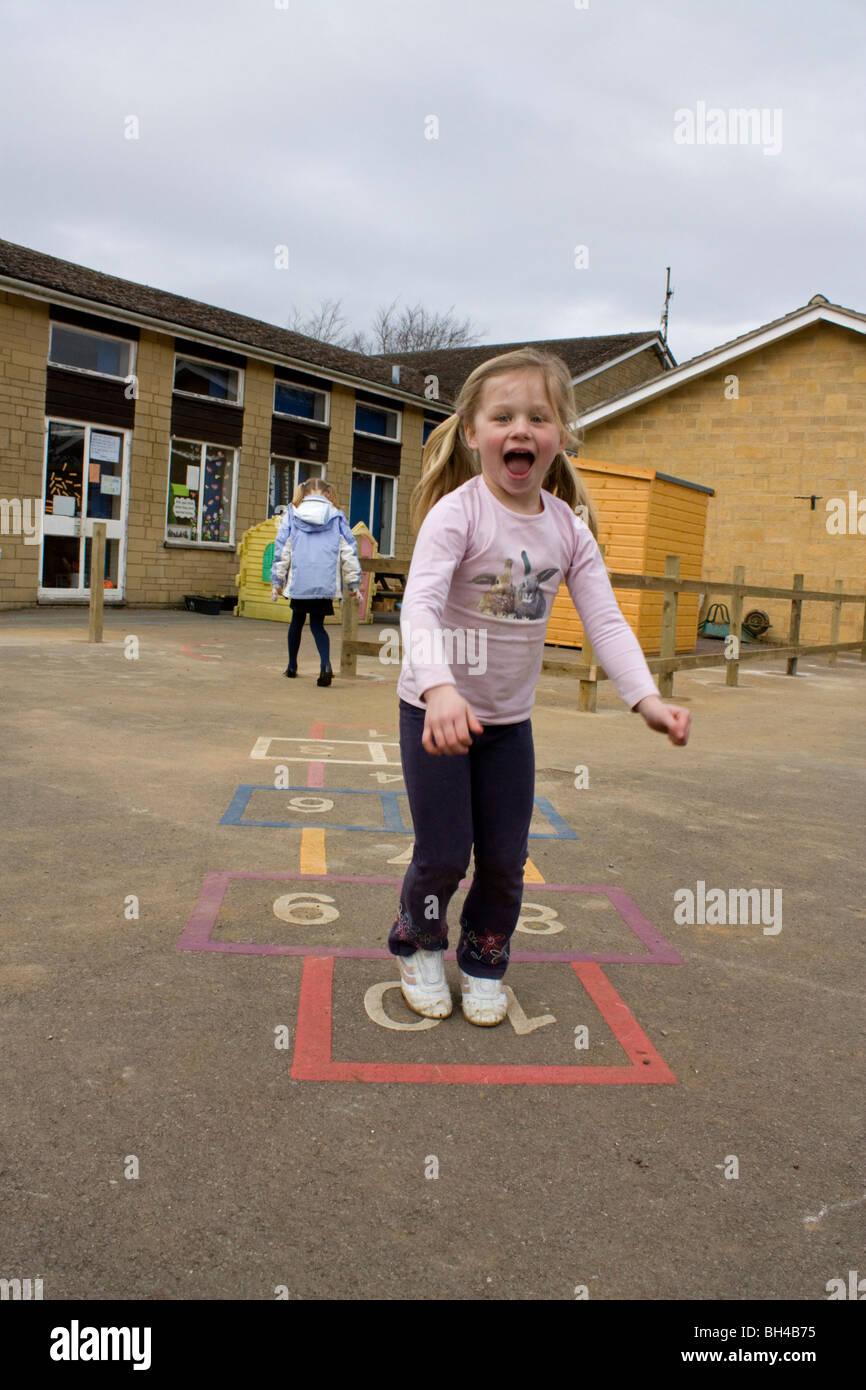 Enfant jouant à la marelle en jeu pour enfants à l'école Photo Stock