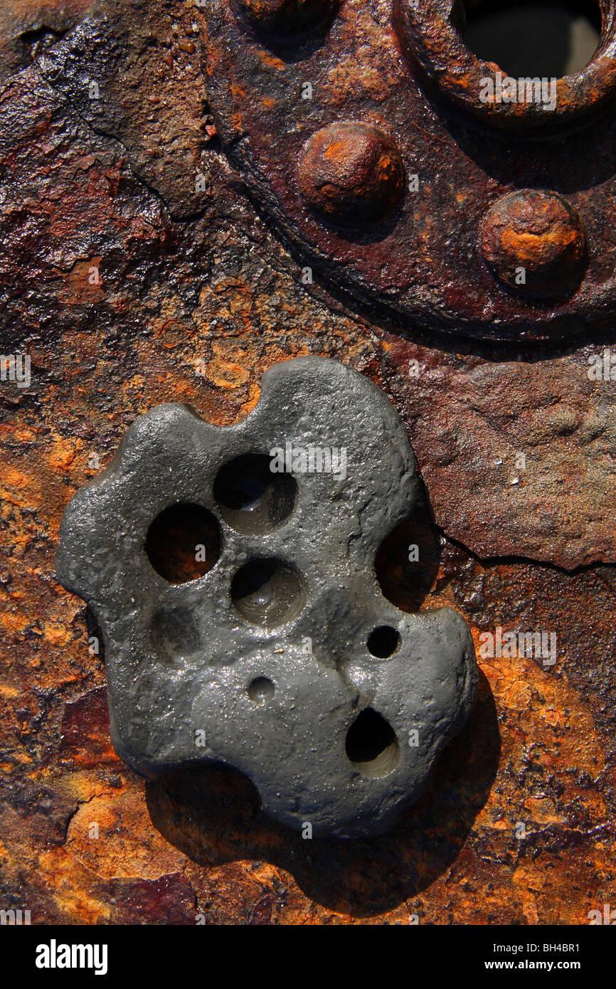 Une pierre avec des trous circulaires érodé sur un vieux baril rouillé avec des rivets qui reflètent Photo Stock