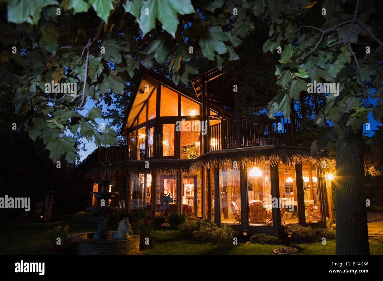 Maison moderne de style tropical avec jardin paysagé au crépuscule, Laval, Québec Photo Stock