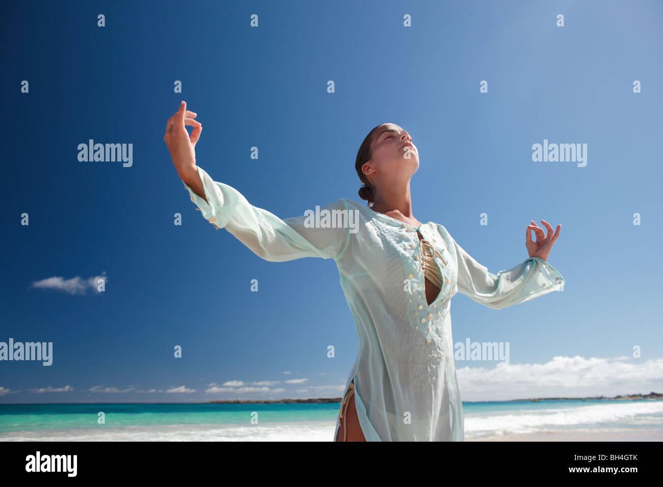 Une jeune femme pratiquant le Tai Chi sur une plage tropicale déserte Photo Stock