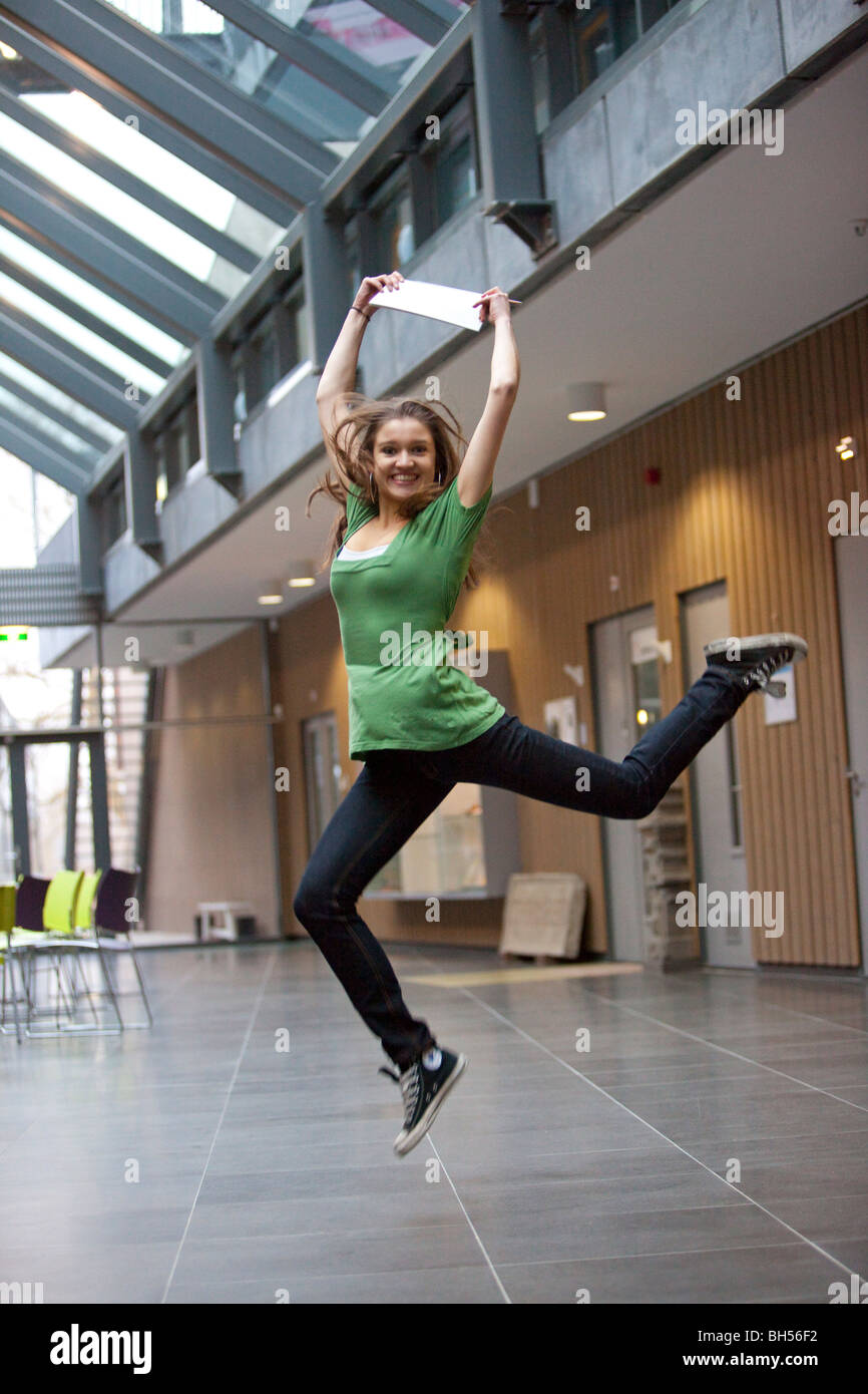 Teenage girl sauter de joie avec son certificat Photo Stock