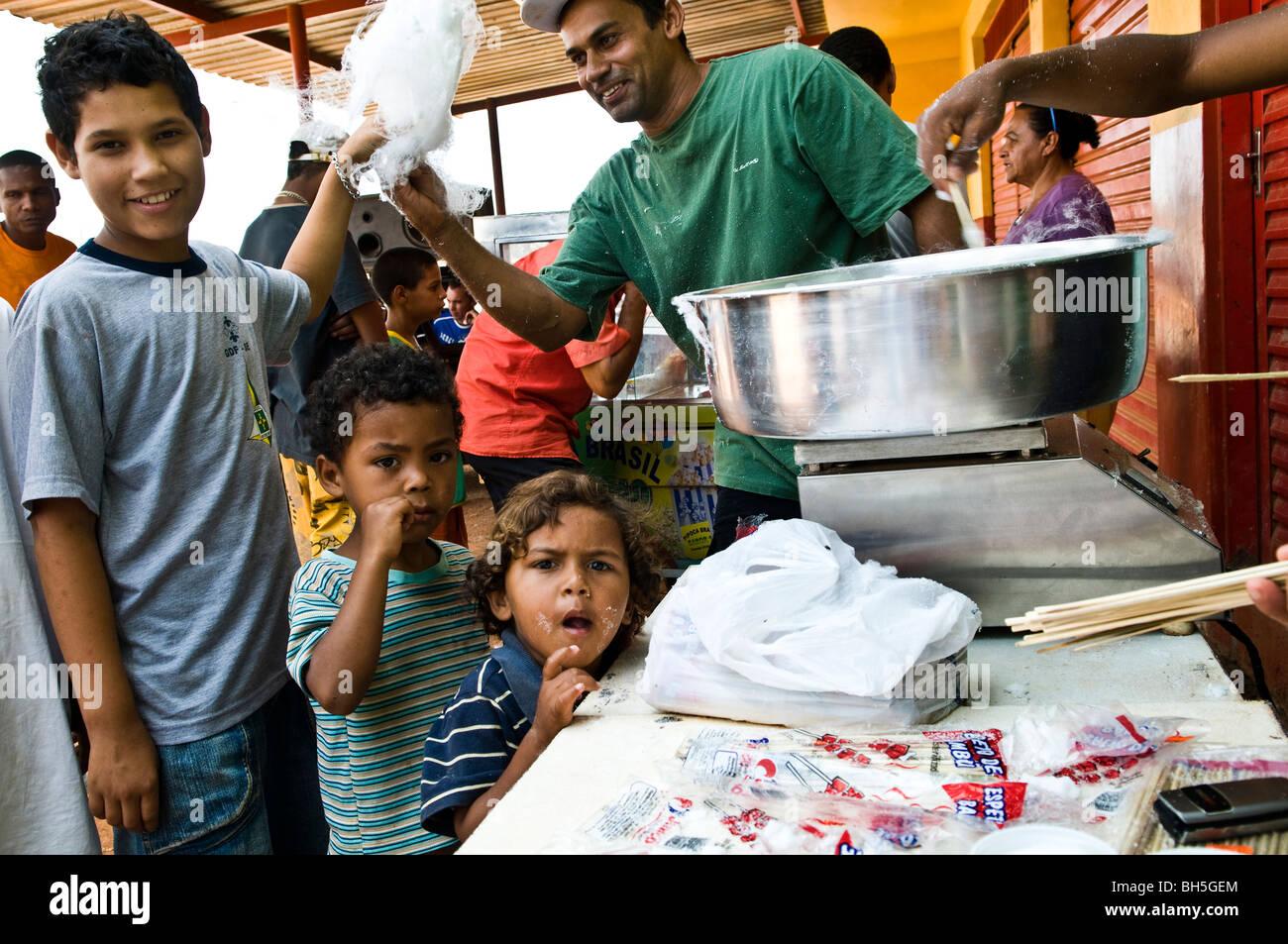 Les enfants bénéficient d'une sucre coton candy dans un quartier pauvre au Brésil. Banque D'Images