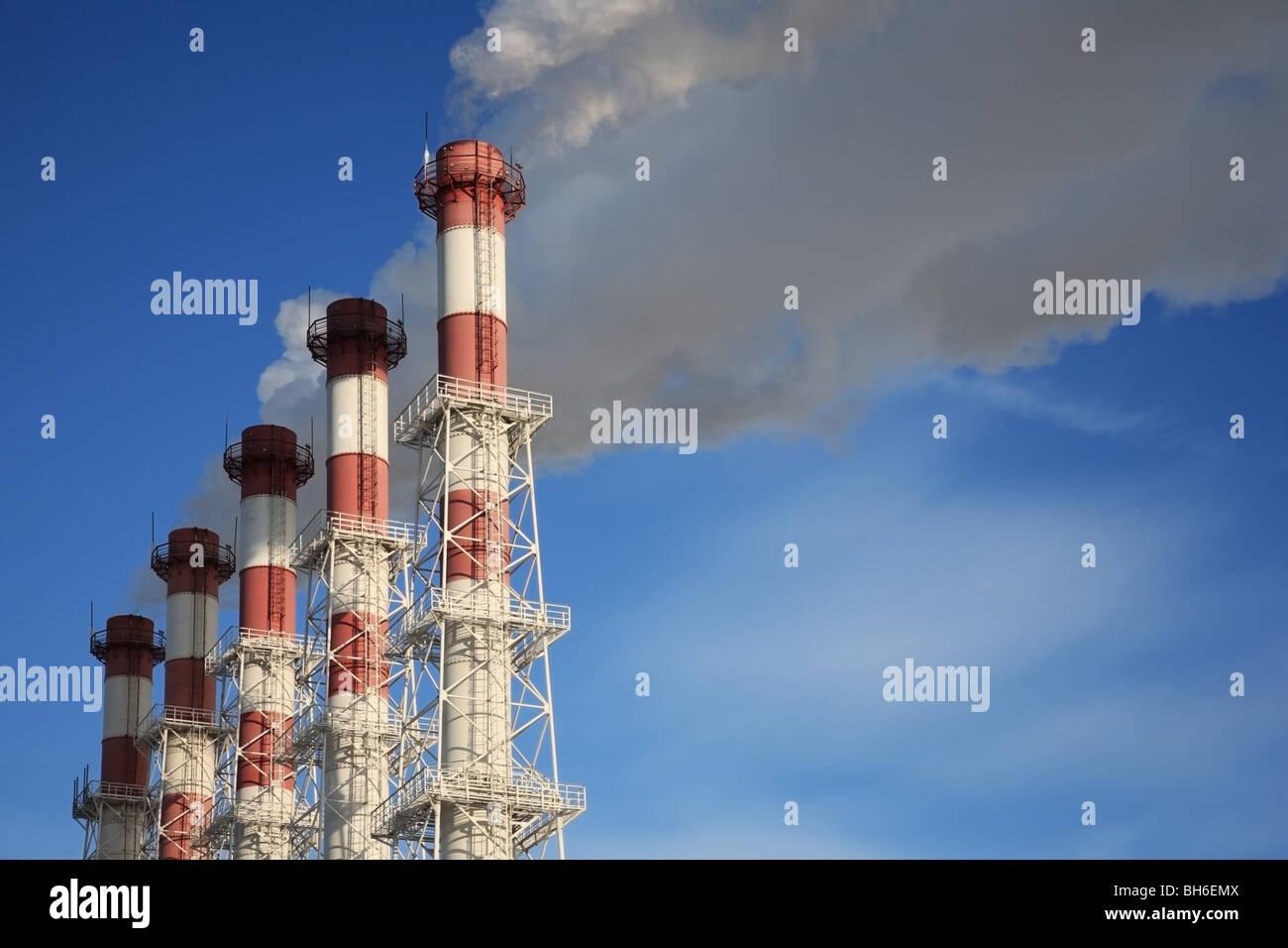 Cinq cheminées avec de la vapeur sur un fond de ciel bleu. Photo Stock