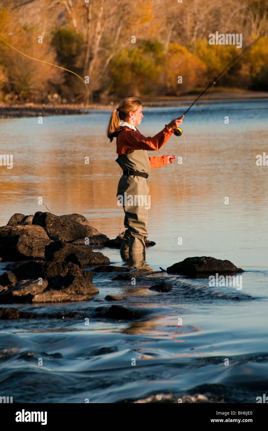 New York, Boise, femme la pêche à la mouche sur la rivière Boise aux couleurs de l'automne. Photo Stock