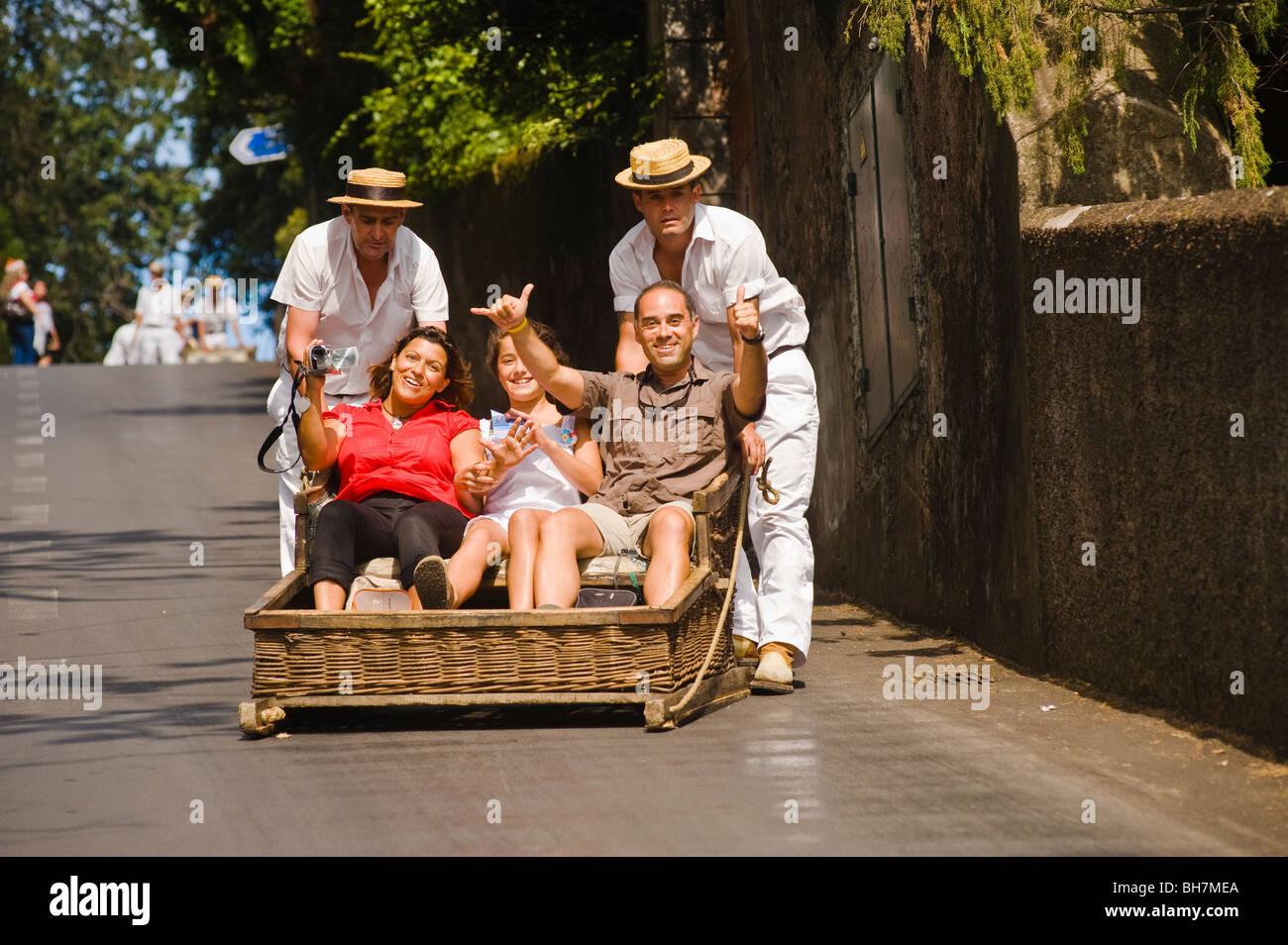 Les touristes se précipitent des rues de Monte dans un tobogan, Funchal, Madère Photo Stock