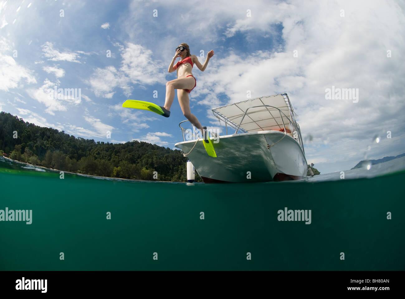 Jeune femme à l'aide de pas de géant du bateau à l'entrée de l'eau pour la plongée Photo Stock