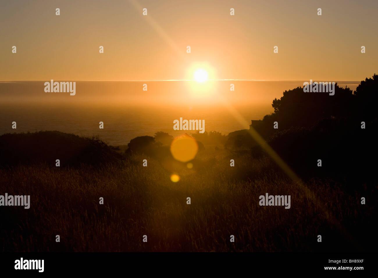 Vue sur le lever de soleil sur la mer et les champs Photo Stock