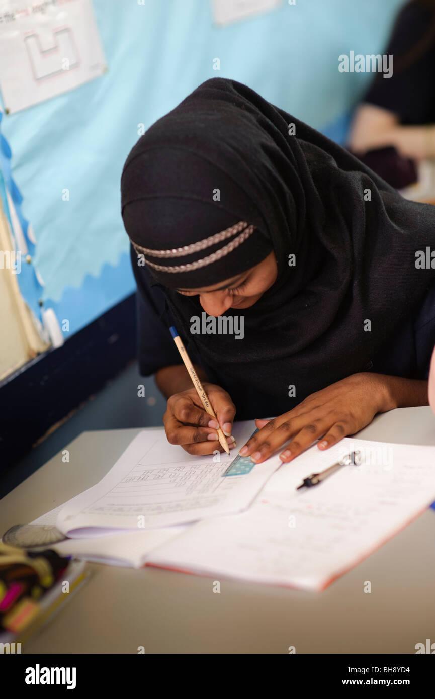 Teenage British Muslim lycéenne écrit dans son ordinateur portable dans une classe de mathématiques, Photo Stock