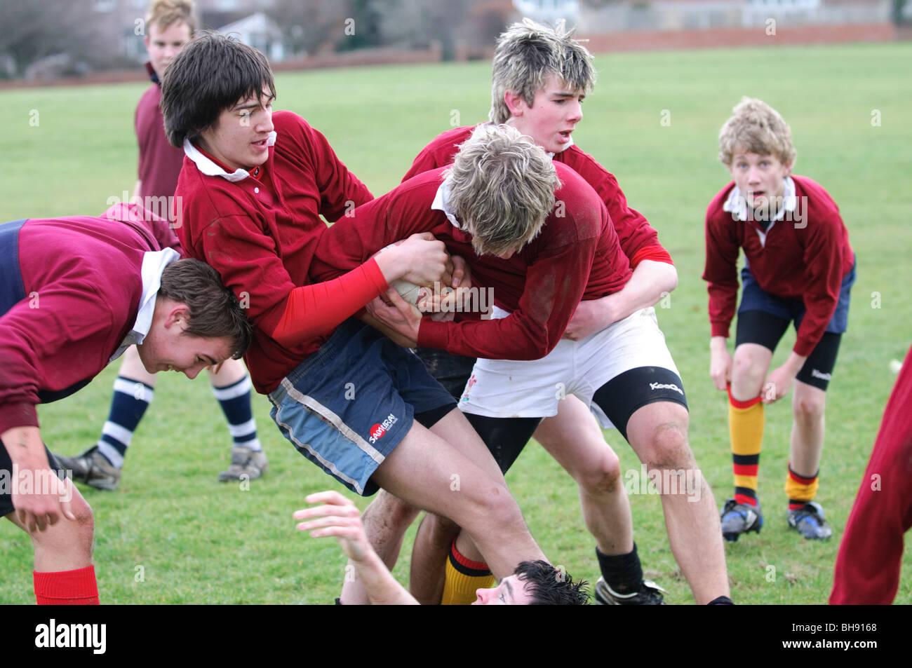 Adolescents jouant un jeu de rugby, sport et jeux d'éducation physique à l'école secondaire, Photo Stock