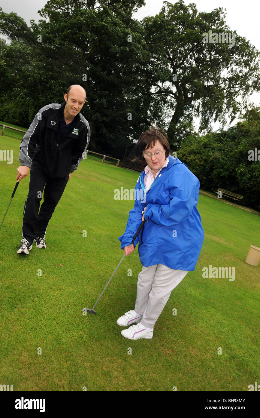 Deux femmes ayant des troubles d'apprentissage jouer pitch and putt, North Yorkshire Banque D'Images