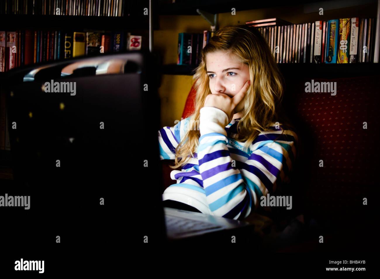 Teenage girl using a laptop computer at home, UK - vérification de son compte de réseau social Facebook Photo Stock