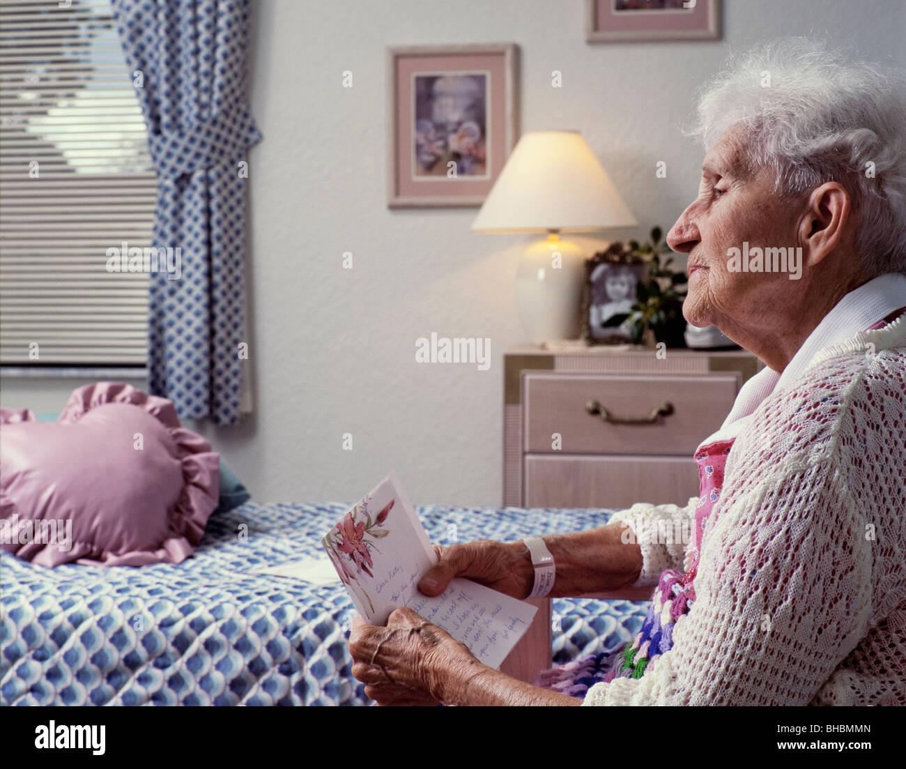 Femme âgée pour lire une lettre envoyée en maison de soins infirmiers Photo Stock