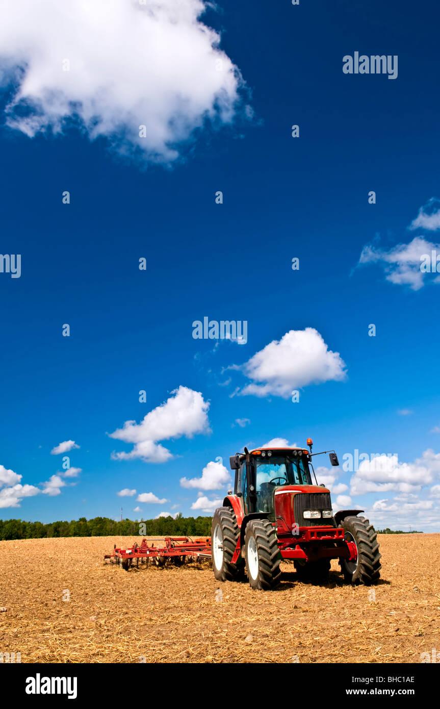 La petite agriculture avec tracteur et charrue dans le champ Photo Stock