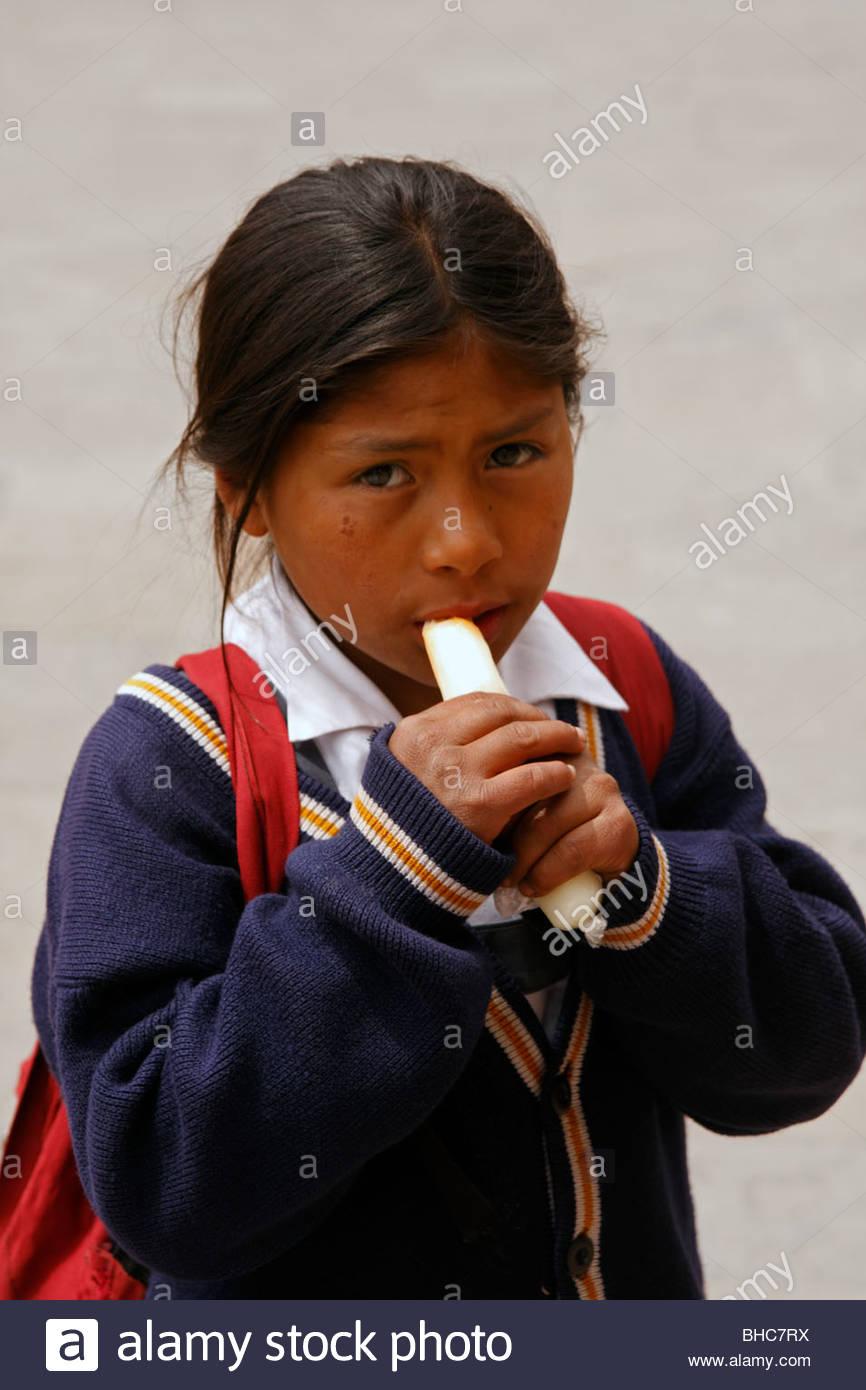 Lycéenne de manger de la canne à sucre, Cuzco, Pérou Photo Stock