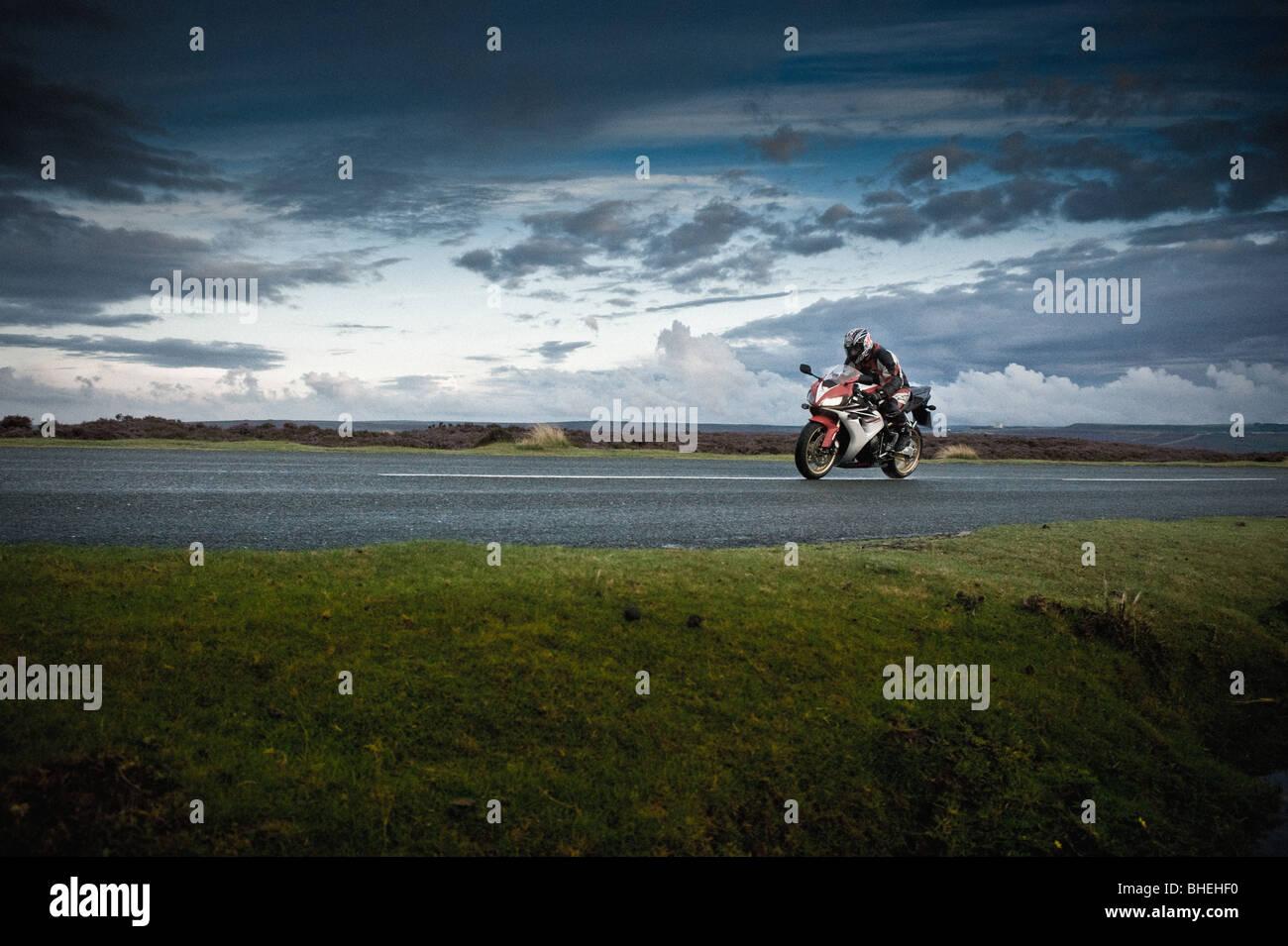 Vue latérale des motos et de rider sur road, North Yorkshire Moors, UK Photo Stock