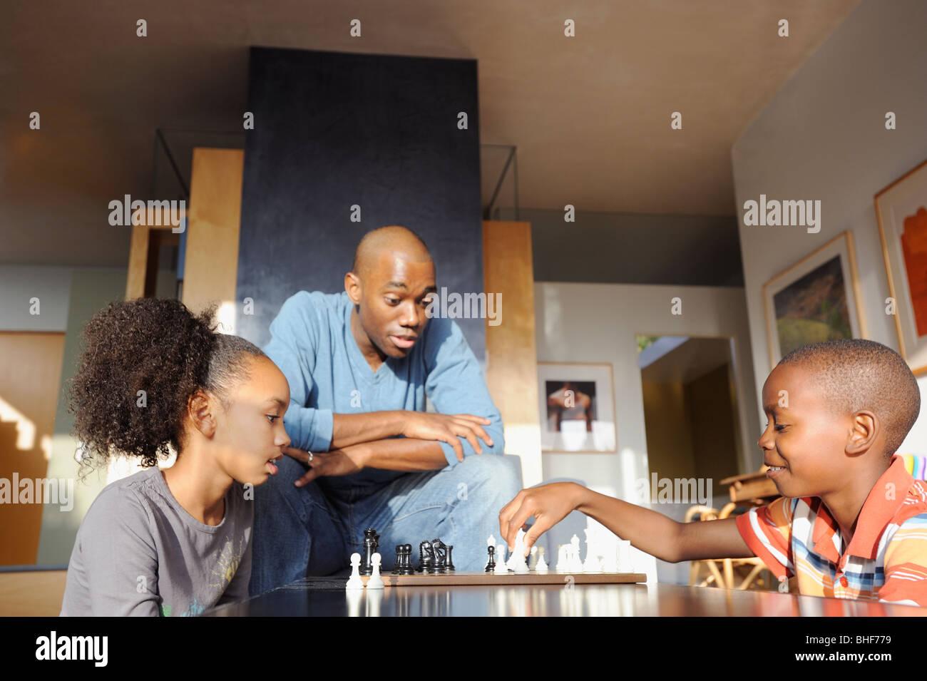 Père noir en regardant les enfants jouer aux échecs Banque D'Images