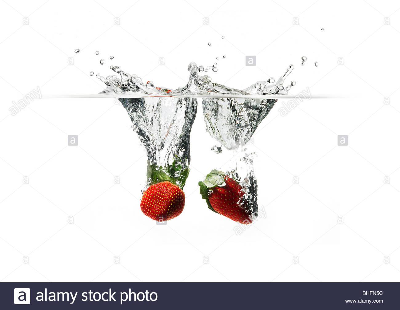 Deux fraises a chuté dans l'eau cristalline de la création d'un splash. Photo Stock