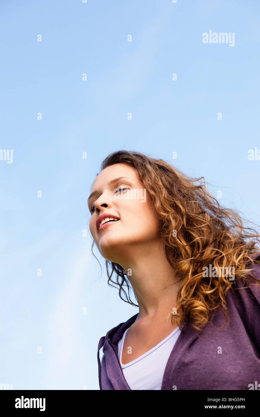 Jeune femme sous ciel bleu Photo Stock