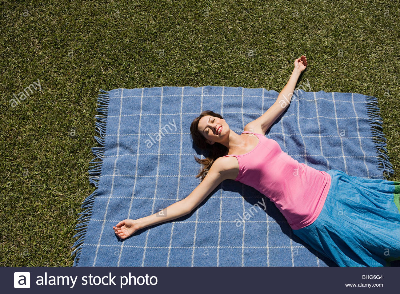 Woman lying on picnic blanket with arms outstretched Photo Stock