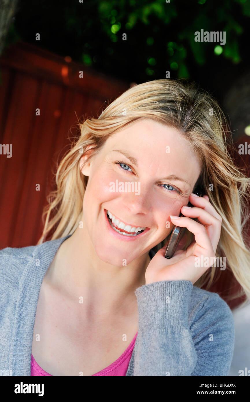Une femme blonde en utilisant son téléphone portable, la Suède. Banque D'Images