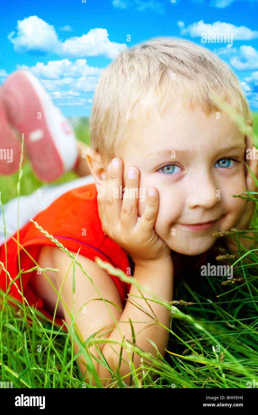 Portrait of happy cute child dans l'herbe Photo Stock