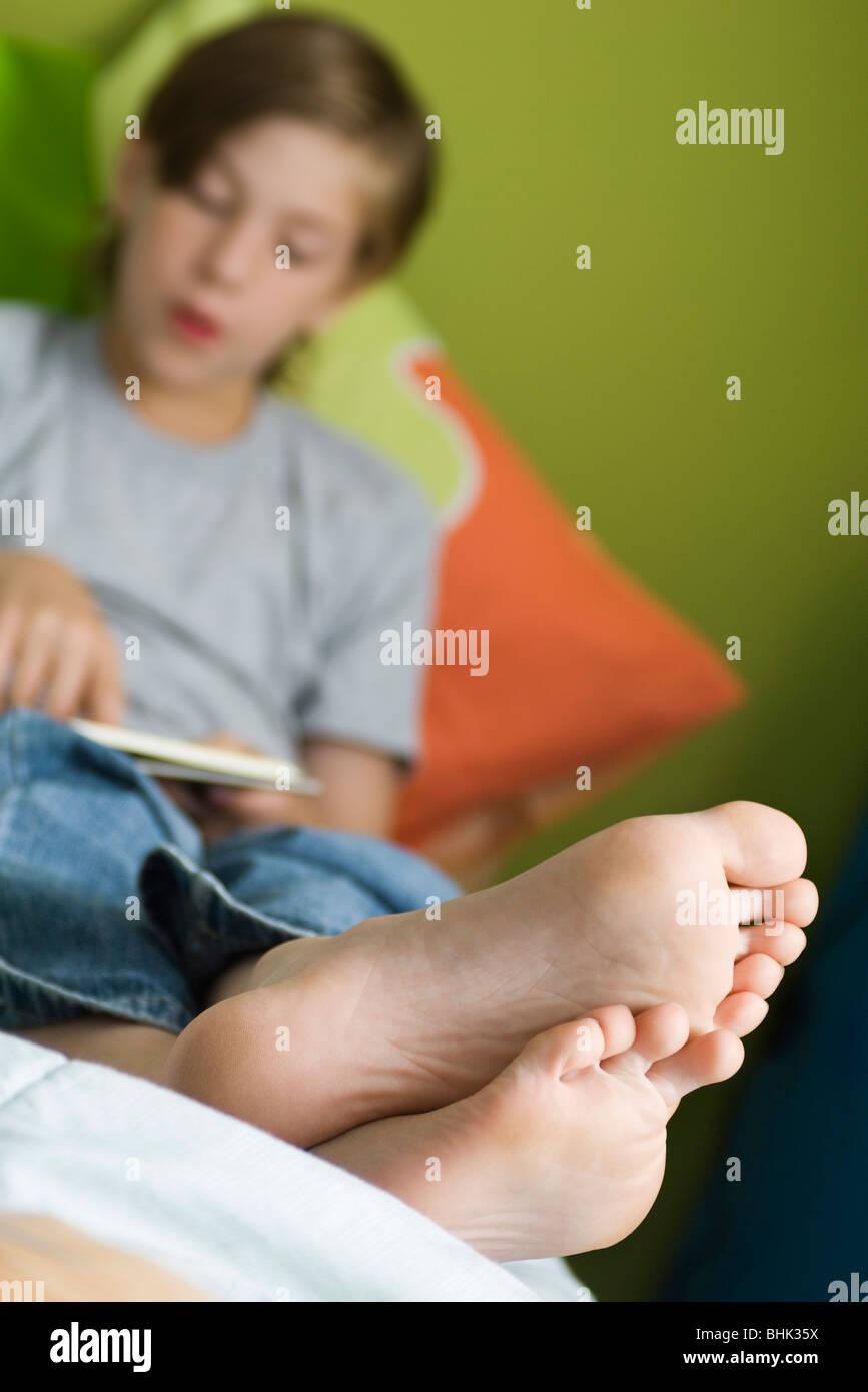 Garçon avec pieds inclinables jusqu'reading book Banque D'Images