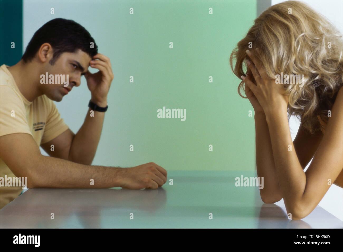Contrarié couple sitting at table, les deux chefs de portefeuille Banque D'Images