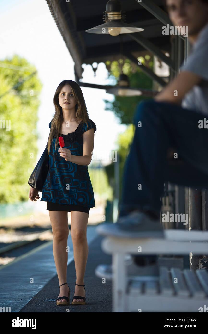 Jeune femme avec ma glace en attente à l'arrêt de bus Banque D'Images