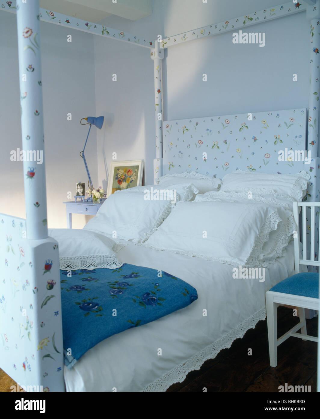 Oreillers et draps blanc peint floral sur lit à baldaquin dans la ...