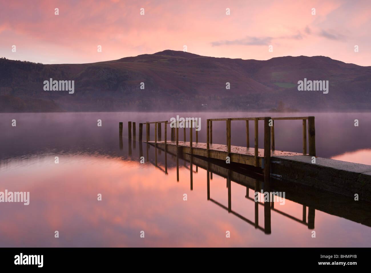 Lever de soleil sur l'eau de Derwent Hawes fin jetty, Parc National de Lake District, Cumbria, England, UK. Photo Stock