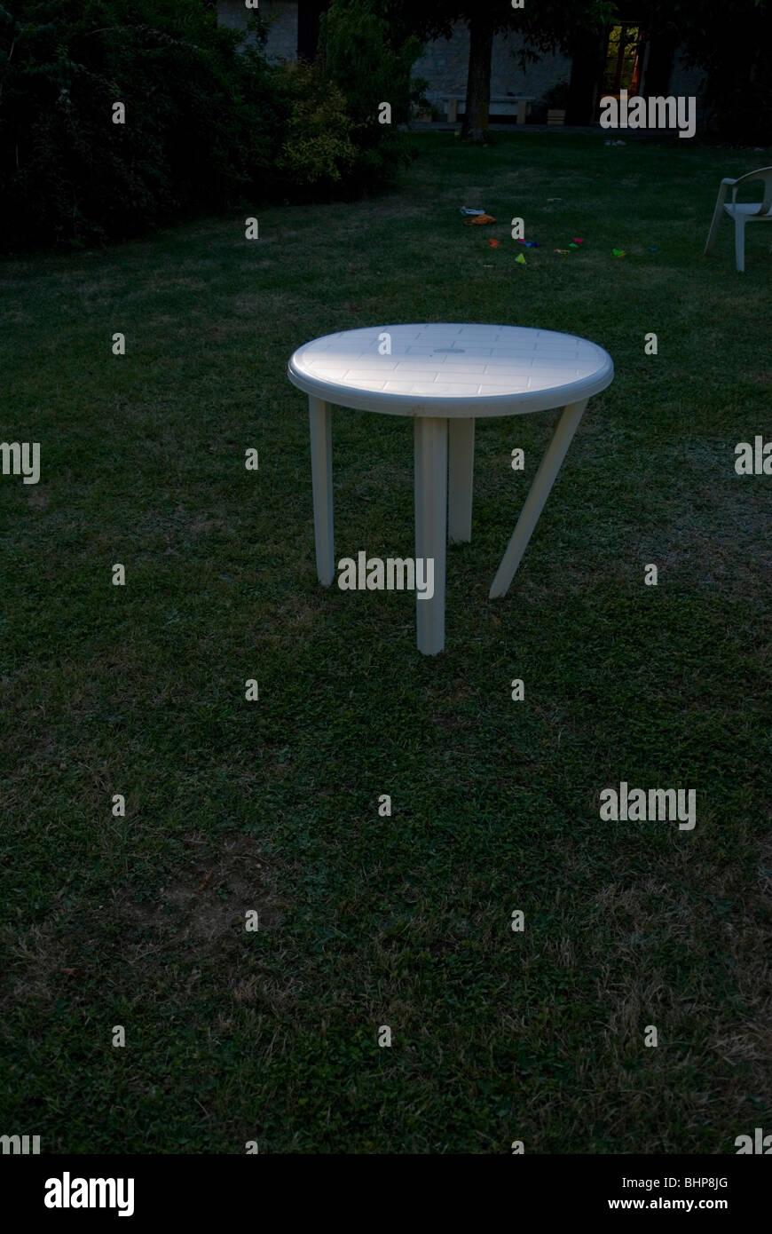 Une image d\'une table de jardin en plastique blanc bancal ...
