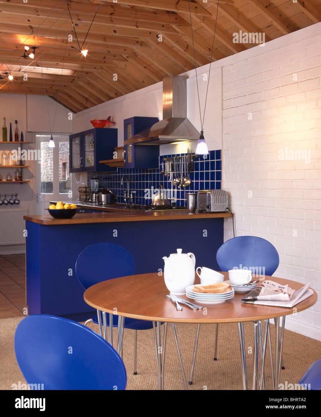 Service à Café Blanc Circulaire Sur Table Avec Chaises Bleues Dans La  Région De Coin Repas De Cuisine Moderne Avec Unités Bleu Vif Et Mur Peint