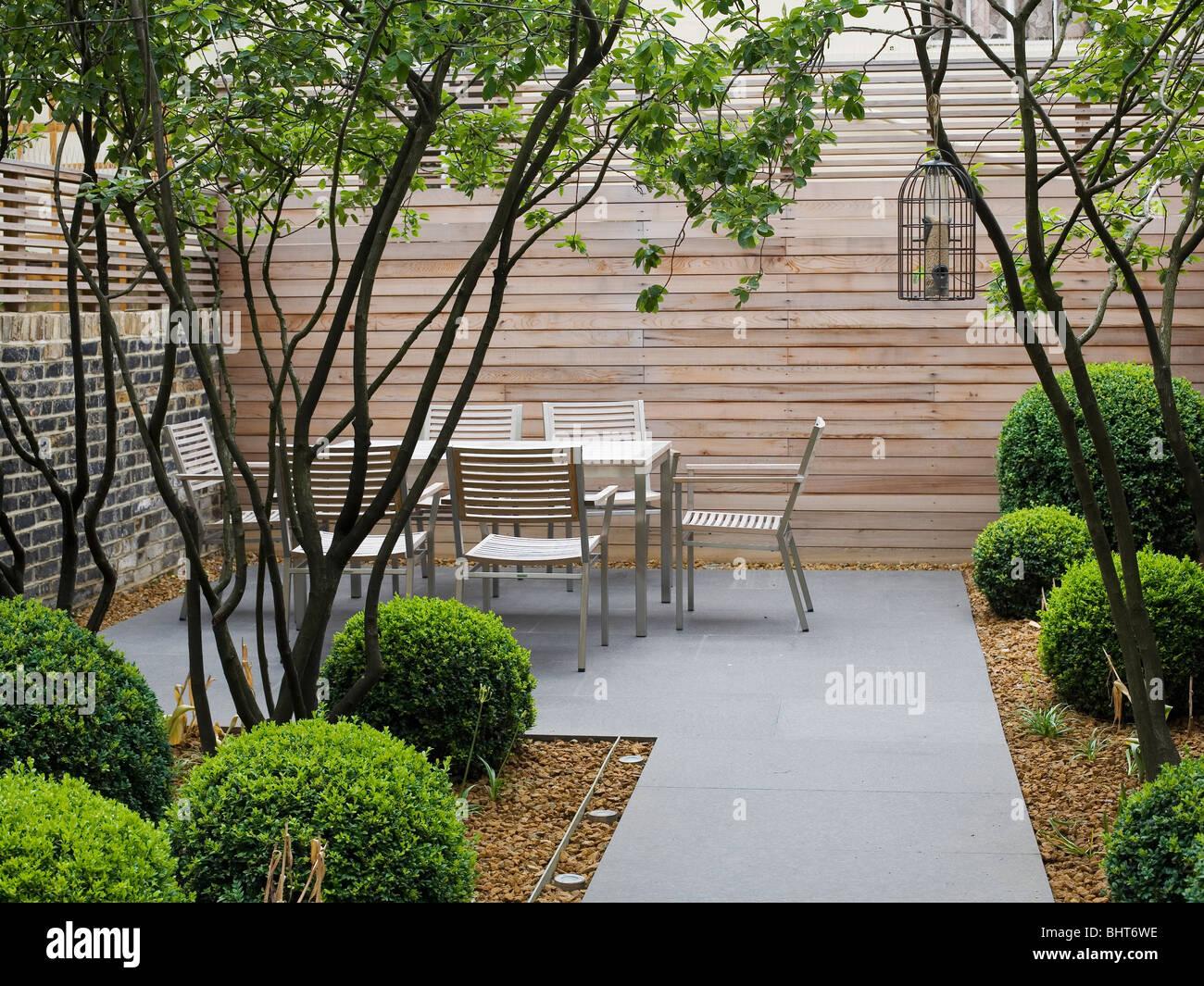 Table et chaises modernes contre tall clôture en bois dans la maison d'architecture Jardin avec arbustes Photo Stock