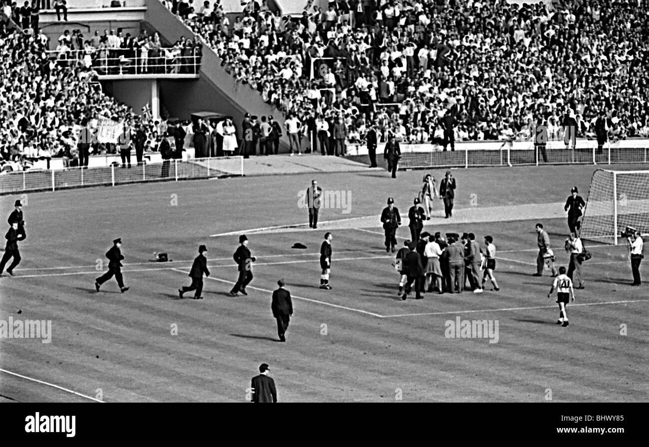 Sur le terrain de la police que l'Angleterre v la Coupe du Monde 1966 Argentine jeu après coup de sifflet final où l'arbitre Rudolph Kreitlin a été confronté à des joueurs argentins en colère en raison d'être Rattin envoyé Banque D'Images