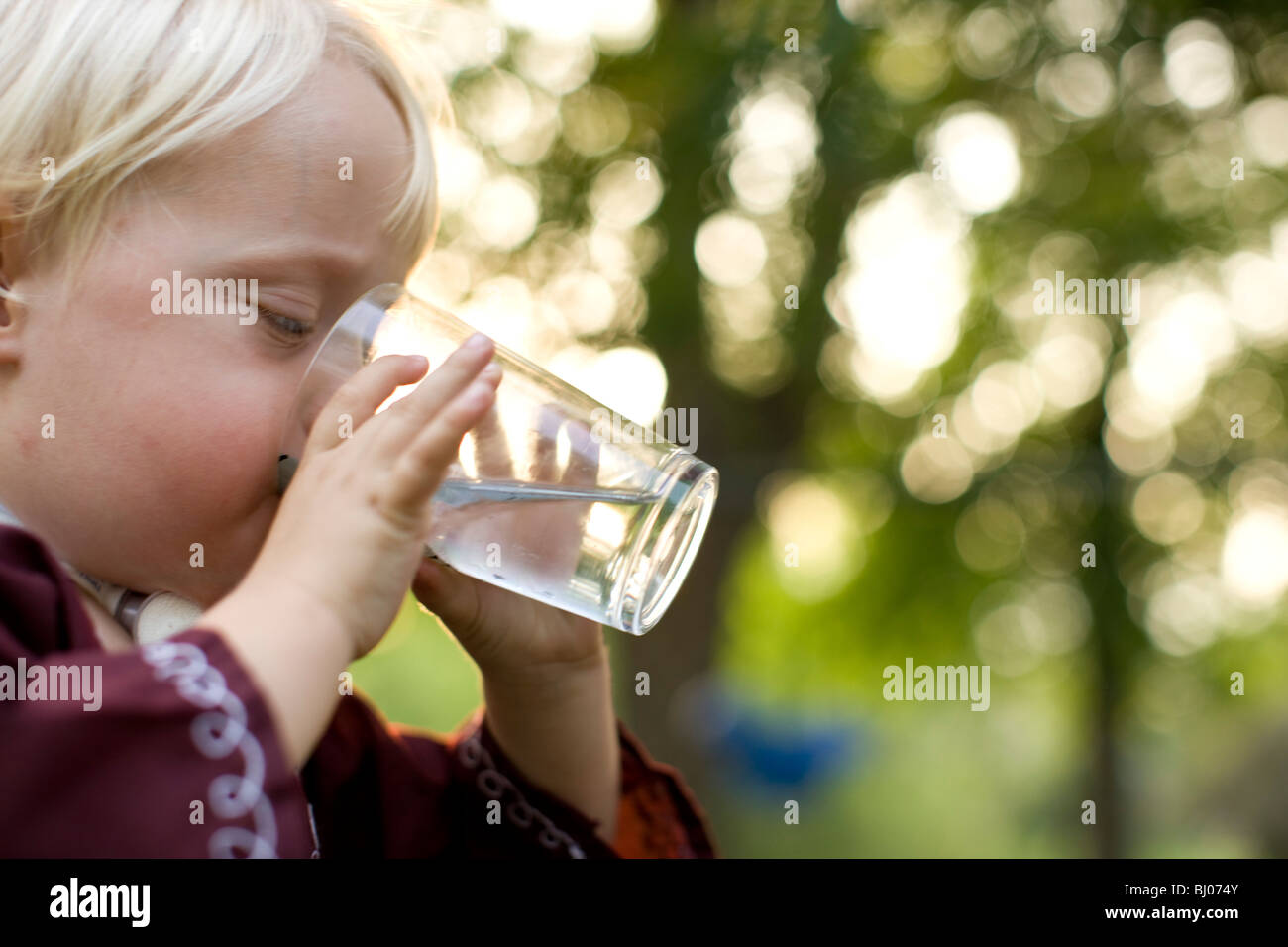 Jeune garçon de boire un verre d'eau. Photo Stock