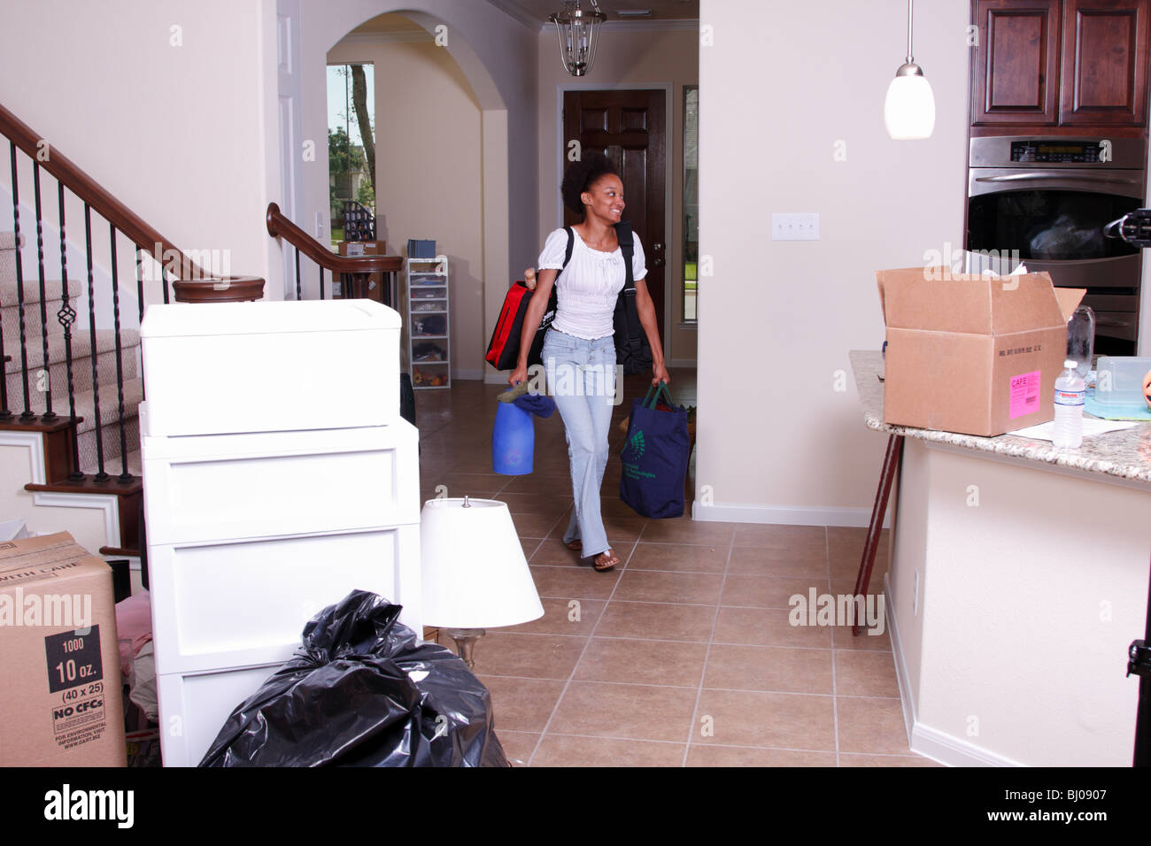 Jeune femme déménagement Retour à l'accueil Photo Stock