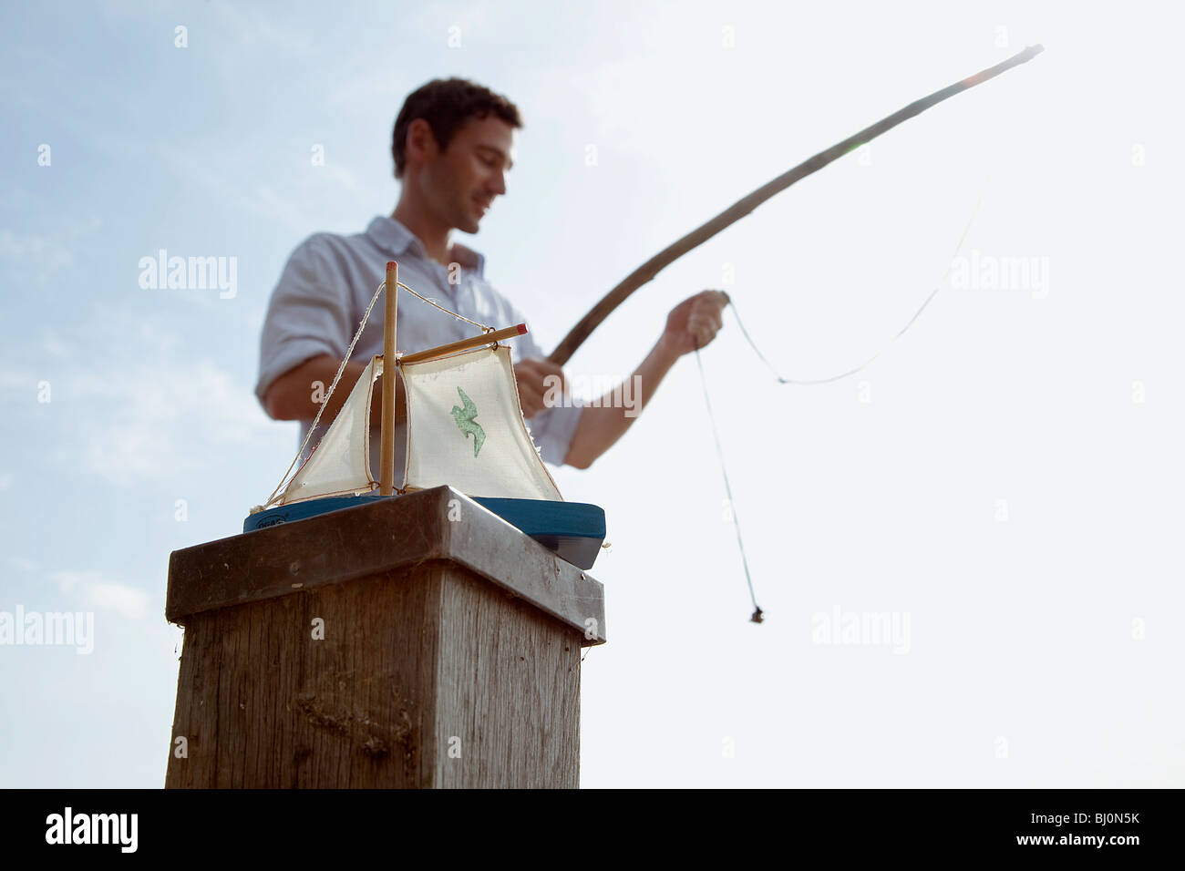 Bateau jouet sur poteau avec angler en arrière-plan Photo Stock