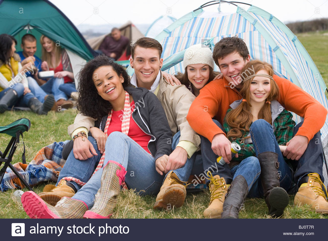 Les couples heureux camping en tente et en assistant à festival en plein air Photo Stock