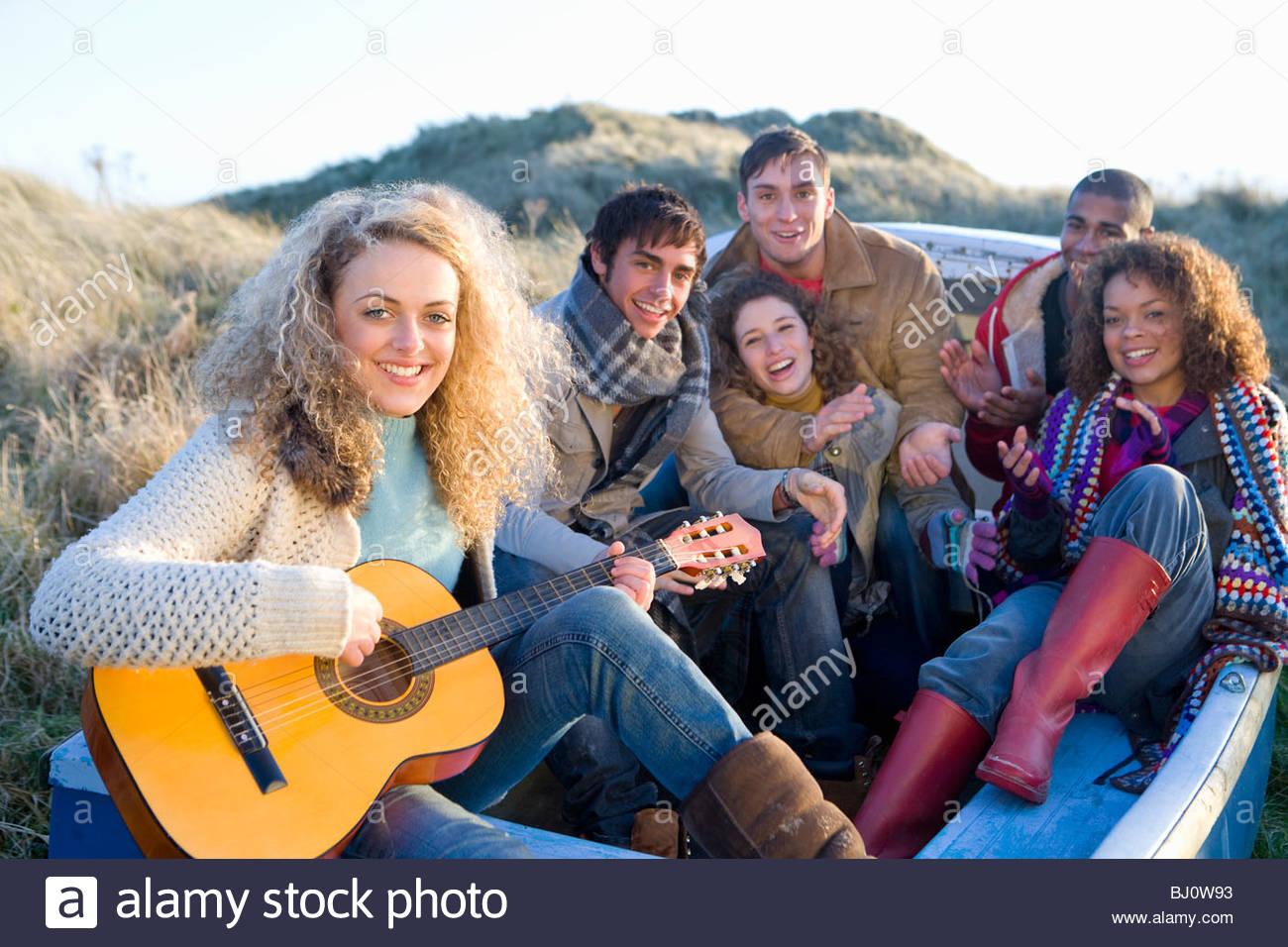 Amis assis dans le bateau en chantant et en s'amusant Photo Stock