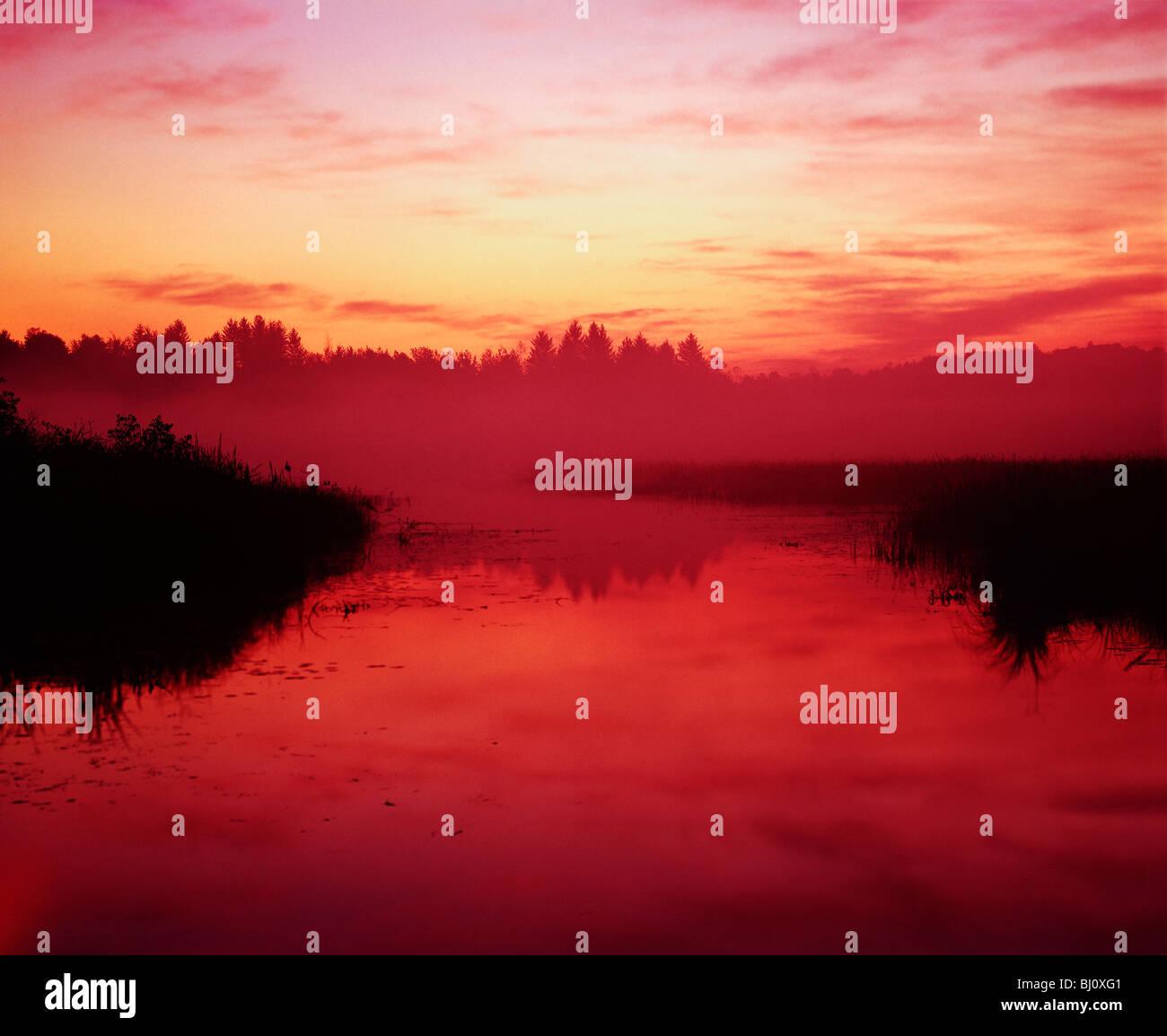 L'aube rouge sky reflète dans Mendon étangs, bassins de Mendon County Park, près de Rochester, Photo Stock